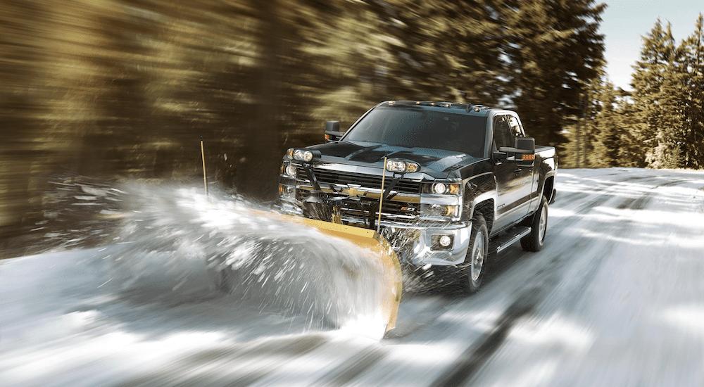 A black Chevy Silverado plowing through snow
